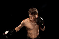 Męski boksera boks w uderzać pięścią torbę z dramatycznym zirytowanym oświetleniem w ciemnym studiu Fotografia Stock