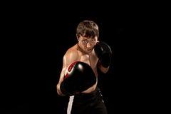 Męski boksera boks w uderzać pięścią torbę z dramatycznym zirytowanym oświetleniem w ciemnym studiu Zdjęcie Royalty Free