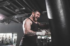 Męski boksera szkolenie z uderzać pięścią torbę w ciemnej sport sala Fotografia Stock