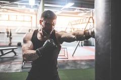 Męski boksera szkolenie z uderzać pięścią torbę w ciemnej sport sala Obraz Stock
