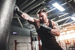 Męski boksera szkolenie z uderzać pięścią torbę w ciemnej sport sala Obraz Royalty Free