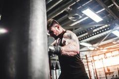 Męski boksera szkolenie z uderzać pięścią torbę w ciemnej sport sala Zdjęcia Stock