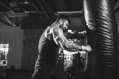 Męski boksera szkolenie z uderzać pięścią torbę w ciemnej sport sala Zdjęcie Stock