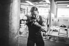 Męski boksera szkolenie z uderzać pięścią torbę w ciemnej sport sala Zdjęcie Royalty Free
