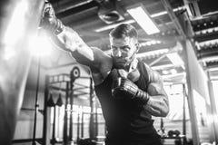 Męski boksera szkolenie z uderzać pięścią torbę w ciemnej sport sala Fotografia Royalty Free