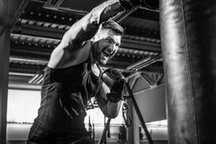 Męski boksera szkolenie z uderzać pięścią torbę w ciemnej sport sala Obrazy Royalty Free
