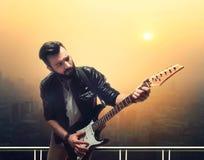 Męski brutalny solo gitarzysta z gitarą elektryczną Obrazy Royalty Free