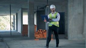 Męski budowa ekspert chodzi wzdłuż budowy z laptopem w jego rękach zbiory