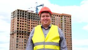 Męski budowniczego brygadier, pracownik lub architekt na budowa placu budowym ono uśmiecha się kamera, zbiory