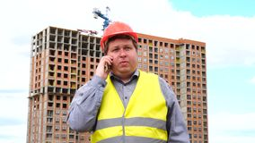 Męski budowniczego brygadier, pracownik lub architekt na budowa placu budowym opowiada jego telefonem, zbiory wideo