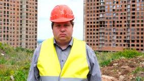Męski budowniczego brygadier, pracownik lub architekt na budowa placu budowym patrzeje kamerę emotionless, zbiory