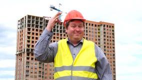 Męski budowniczego brygadier, pracownik lub architekt na budowa placu budowym pokazuje nowego domowego klucz, podczas gdy ono uśm zbiory