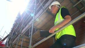 Męski budowniczego brygadier, pracownik lub architekt pracuje na budowa placu budowego pozycji na rusztowaniu, zdjęcie wideo