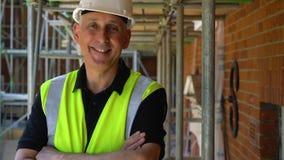 Męski budowniczy na budowa placu budowego pozycji na rusztowaniu z ręki składał roześmianego i ono uśmiecha się kamera zbiory wideo