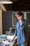 Męski cieśla w ciesielka sklepie na telefonie, mężczyzna przy pracą, lif Fotografia Royalty Free