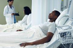 Męski cierpliwy dosypianie w łóżku w oddziale przy szpitalem fotografia royalty free
