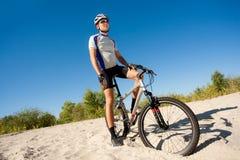 Męski cyklista jedzie rower zatrzymywał staczać się na piasku Zdjęcia Stock