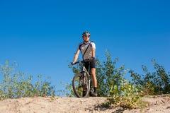 Męski cyklista jedzie rower zatrzymywał staczać się na piasku Fotografia Royalty Free