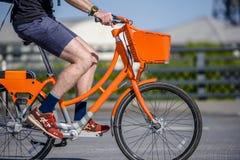 Męski cyklista jedzie społecznie dzierżawiącego pomarańczowego bicykl z koszem na rozdrożu na miasto ulicie fotografia stock