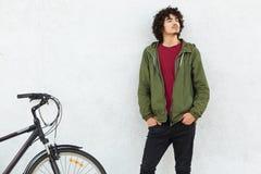 Męski cyklista ubierający w modnym stroju, kędzierzawego włosy, utrzymanie ręki w kieszeni spodnia, małą brodę, patrzeje thoghtfu zdjęcia royalty free