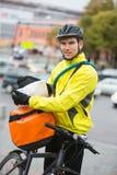 Męski cyklisty kładzenia pakunek W kurier torbie Dalej Fotografia Stock