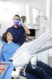Męski dentysta Egzamininuje pacjenta Przy Dentis Podczas gdy Pomocniczy działanie Zdjęcie Stock