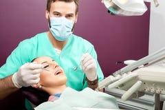 Męski dentysta egzamininuje usta kobieta na dentysty krześle Zdjęcie Royalty Free