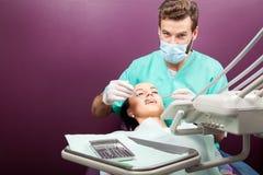 Męski dentysta egzamininuje usta kobieta na dentysty krześle Obrazy Stock