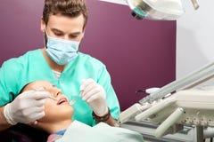 Męski dentysta egzamininuje usta kobieta na dentysty krześle Zdjęcia Royalty Free