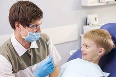 Męski dentysta egzamininuje zęby cierpliwa rozochocona chłopiec Zdjęcia Royalty Free