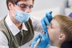 Męski dentysta egzamininuje zęby cierpliwa rozochocona chłopiec Obrazy Royalty Free