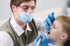 Męski dentysta egzamininuje zęby cierpliwa rozochocona chłopiec Zdjęcie Royalty Free