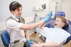 Męski dentysta egzamininuje zęby cierpliwa rozochocona chłopiec Obraz Royalty Free