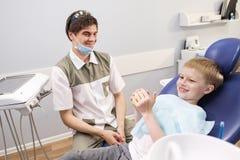 Męski dentysta egzamininuje zęby cierpliwa rozochocona chłopiec obrazy stock