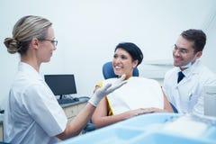 Męski dentysta i asystent z żeńskim pacjentem Zdjęcie Stock