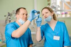 Męski dentysta pokazuje promieniowanie rentgenowskie żeński asystent przy stomatologiczną kliniką Zdjęcia Royalty Free