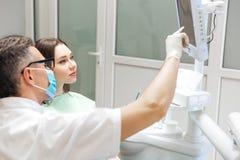 Męski dentysta przegląda jej xray na ekranie komputerowym Obrazy Royalty Free