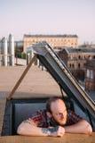 Męski dopatrywanie zmierzch na dachu Kreatywnie czas wolny obraz stock