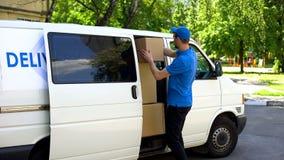 Męski doręczeniowy pracownik bierze karton od samochodu dostawczego, drobnicowa transport usługa obrazy stock