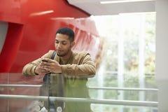 Męski dorosły studencki używa smartphone w nowożytnym uniwersyteckim budynku Zdjęcie Stock