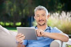 Męski dozorca Używa pastylka komputer Zdjęcia Royalty Free