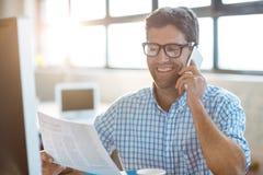 Męski dyrektor wykonawczy opowiada na telefonie komórkowym podczas gdy czytający gazetę Zdjęcia Royalty Free