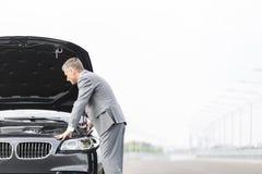 Męski dyrektor wykonawczy patrzeje awaria samochód przeciw niebu fotografia stock