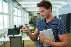 Męski dyrektor wykonawczy używa na telefonie komórkowym w biurze Zdjęcie Stock
