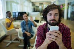 Męski dyrektor wykonawczy używa na telefonie komórkowym w biurze Zdjęcia Stock
