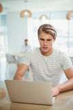 Męski dyrektora wykonawczego obsiadanie przy biurkiem i używać laptopem Zdjęcie Stock
