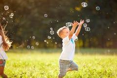 Męski dziecko łapie mydlanych bąble w naturze Zdjęcie Royalty Free