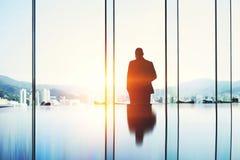 Męski ekonomista podczas gdy stoi w nowożytnym drapacza chmur wnętrzu przeciw okno z kopii przestrzenią Obrazy Royalty Free