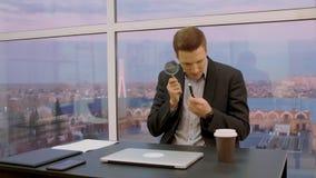 Męski ekspert sprawdza pióro z powiększać - szkło podczas gdy siedzący przy miejsce pracy zbiory wideo