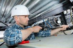 Męski elektryk instaluje światło na suficie na stepladder fotografia stock